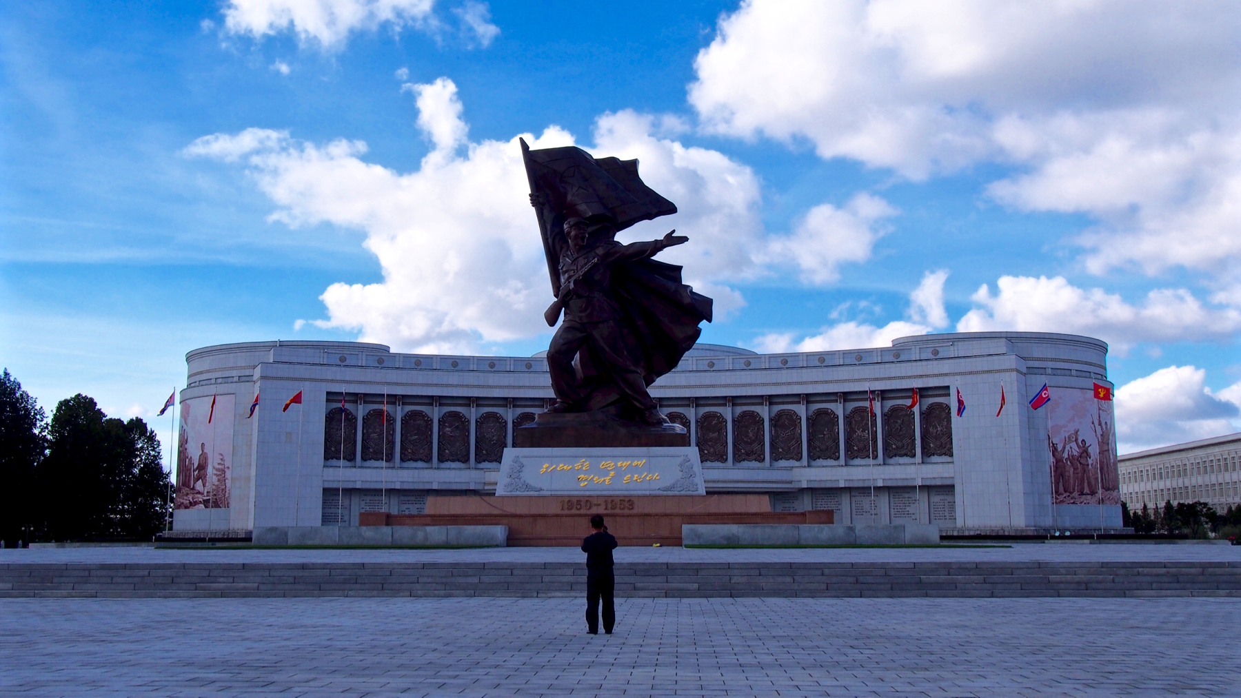 The war museum in Pyongyang, depicting a revolutionary soldier raising the flag of the DPRK. Our cameraman captures the moment we arrive, just as he captures all moments.